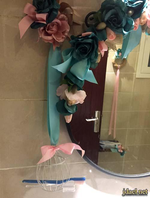 تزيين مرايا الحمام واطواق الفلين بالورد بالوان زاهية بشرايط الخيش